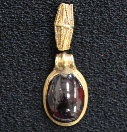 photograph of gold pendant and bead