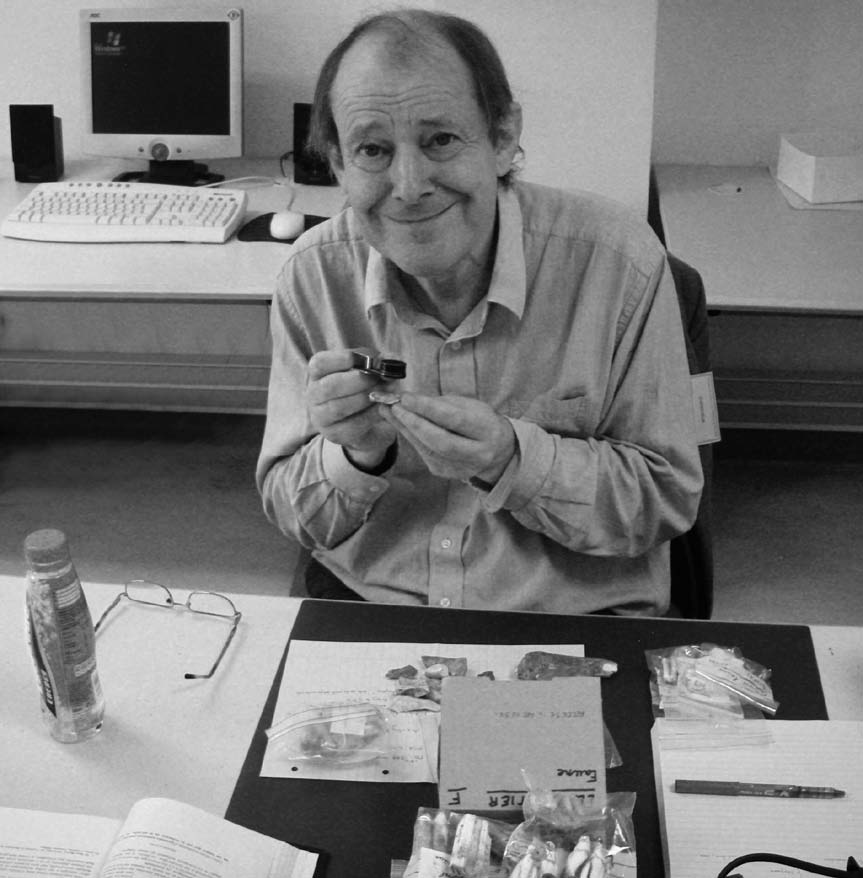 A black and white photograph of Roger Jacobi using an hand led magnifying glass identifying artefacts
