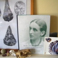 a framed picture of flints and a book with portrait of Nina Layard