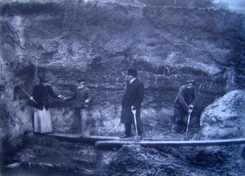 Photograph of Nina in the excavation with three men