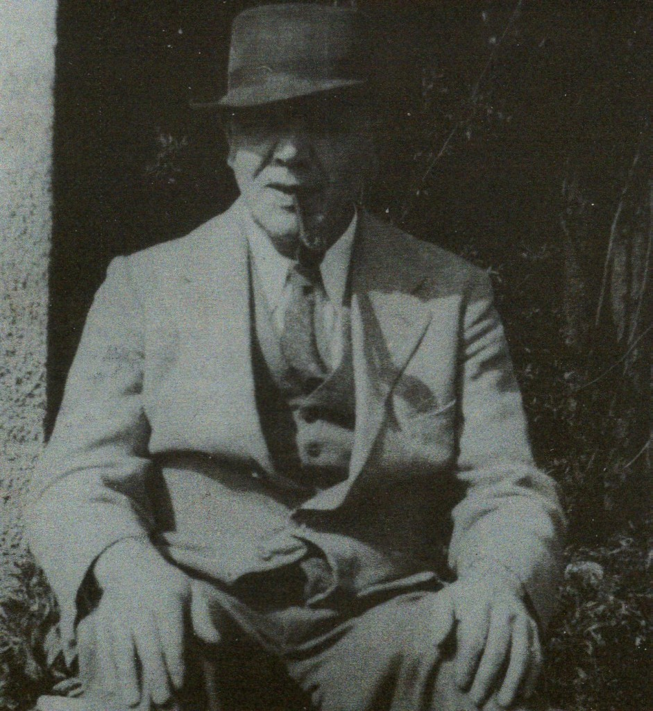 A black and white photograph of James Reid Moir sitting down with pipe and hat.