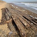 wooden planks on sandy beach next to sea