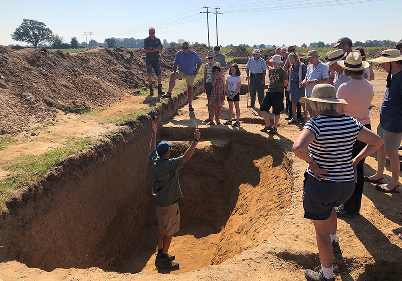 many people standing in trench around excavated ditch