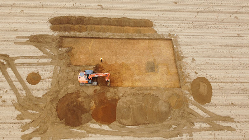 aerial view of digger on field