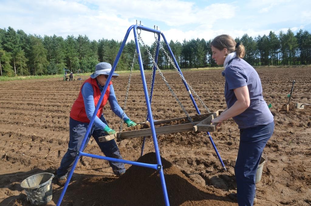 two people sieving soil in field