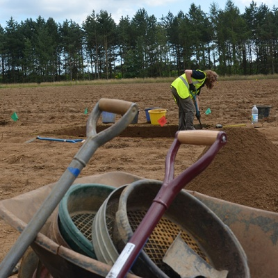 tools in a wheel barrow and person in a field excavating
