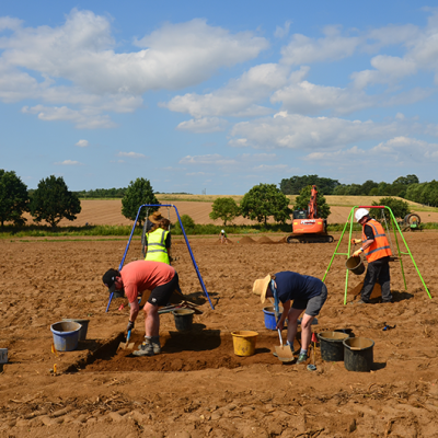 sandy field, people digging and machine in background