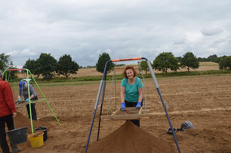 people sieving soil in field