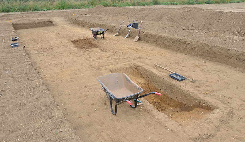 wheelbarrows and spades in a trench