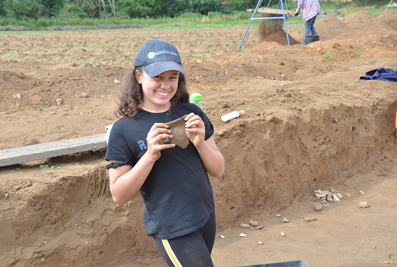 young person smiling holding a large fragment of pottery