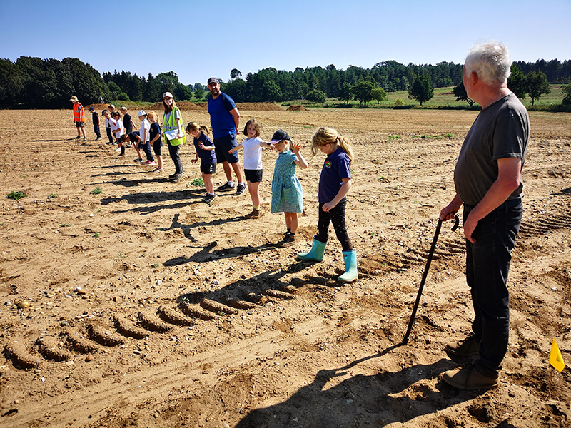 kids and adults standing in a line in a field