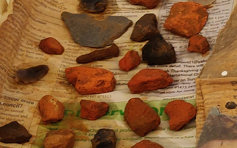 fragments of orange brick placed on newspaper