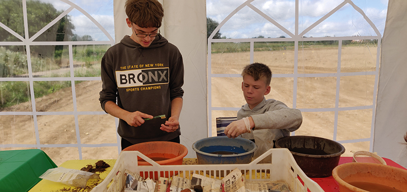 two people washing finds using toothbrushes and bowls